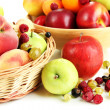 Stock Photo: Assortment of juicy fruits in wicker basket and wooden bowl, isolated on white