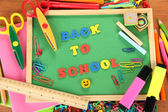 Small chalkboard with school supplies on wooden background. Back to School — Stock Photo