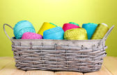 Bright threads in basket on wooden table on green background — Stock Photo