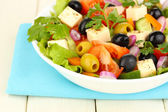 Fresh salad in plate on wooden table — Stock Photo