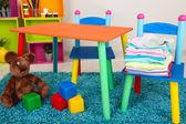 Pequeña y colorida mesa y sillas con ropa de bebé — Foto de Stock
