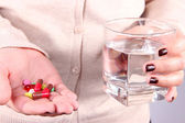 Many pills and glass water in hand — Stock Photo