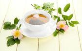 Tisane de fleurs de roses hip sur table en bois blanc — Photo