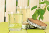 Glasses of birch sap on green wooden table — Stock Photo