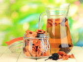 Assorted dried fruits in bank and compote of dried fruits on wooden table on natural background — Stock Photo