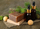 Hand-made soap and bottles of fir tree oil on wooden background — Stock Photo