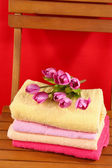 Towels and flowers on wooden chair on red background — Stock Photo