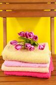 Handtücher und blumen auf holzstuhl auf gelbem grund — Stockfoto