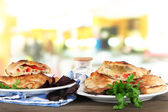Pizza calzones on plates on table on room background — Stock Photo