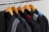 Garnitury i krawaty na wieszaki na szarym tle — Zdjęcie stockowe