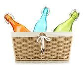 Color glass bottles in wicker basket, isolated on white — Stock Photo