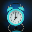 Blue alarm clock on dark blue background — Stock Photo