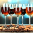 Glasses of liquors with almonds and coffee grains, on bright background — Stock Photo #28605679