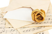 Old envelope with blank paper with dried rose on music sheets close up — Stock Photo
