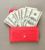 Sac à main avec cent billets de dollar, sur fond de couleur — Photo