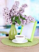 Beautiful lilac flowers on table in room — Stock Photo
