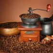 Stock Photo: Coffee grinder, turk and coffee beans on brown background