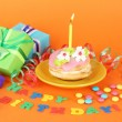 Colorful birthday cake with candle and gifts on orange background — Stock Photo