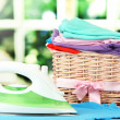 Steam iron and wicker basket with clothes, on bright background — Stock Photo