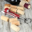 Stock Photo: Corkscrew with wine corks and bottle of wine on wooden table close-up