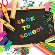 Foto Stock: Small chalkboard with school supplies on white background. Back to School