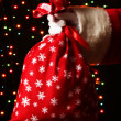 Santa Claus hand holding bag of gifts on bright background — Stock Photo