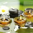 Spa stones with flowers and candles in water on plate — Foto Stock