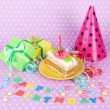 Stock Photo: Colorful birthday cake with candle and gifts on pink background