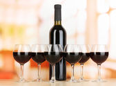 Red wine in glass and bottle on room background — Stock Photo
