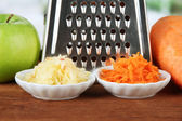 Metal grater and apple, carrot, on bright background — Stock Photo