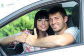 Beautiful happy young couple driving car — Stock Photo