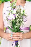 Femme tenant le bouquet, sur fond bleu, sur fond clair, gros plan — Photo