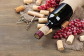 Bottle of wine, grapes and corks on wooden background — 图库照片