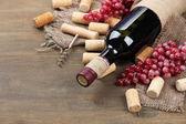 Flasche wein, trauben und korken auf hölzernen hintergrund — Stockfoto