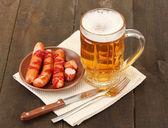 Bier und gegrillten würstchen auf hölzernen hintergrund — Stockfoto