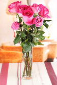Beautiful pink roses in vase on table on room background — Stock Photo
