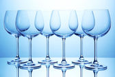 Empty wine glasses arranged on blue background — Stock Photo