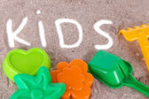 Various children's toys on sand — Stock Photo