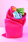 Bolsa rosa com presentes em fundo rosa — Fotografia Stock