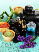 Spas composition with oils and spa stones on wooden table close-up — Stock Photo