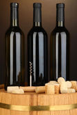 Wine and corks on barrel on brown background — Stock Photo