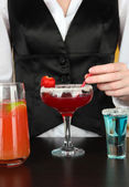 Barmen making tasty cocktails, on bright background — Stock Photo