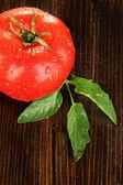 Fresh tomato on wooden background — Stock Photo