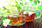 Cup of tea with jasmine, on bamboo mat, close-up — Stock Photo