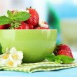 Ripe sweet strawberries in green bowl on blue wooden table — Stock Photo