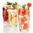 Glasses of fruit drinks with ice cubes isolated on white — Stock Photo