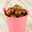 Stock Photo: Fresh gooseberries in bucket on table close-up