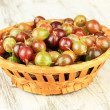 Stock Photo: Fresh gooseberries in wicker basket on table close-up