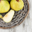 Pears on braided tray on wooden table — Stock Photo #28651225