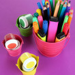 Gouache paint, pens and markers of various colors in baskets on purple background — Stock Photo